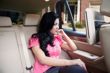 Woman looking out the backseat window of a car